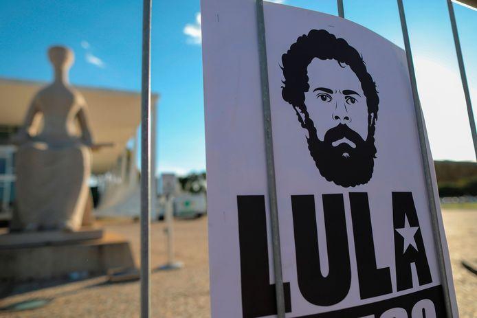 Een cartoon van de voormalige president Luiz Inacio Lula da Silva is door zijn aanhangers aan het hek van het federale gerechtshof in Brasilia gehangen.