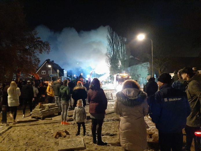 Omstanders kijken toe naar hoe de brand wordt geblust.
