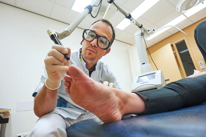 Dermatoloog Ronald Frank 'lasert' de voet van een patiënt