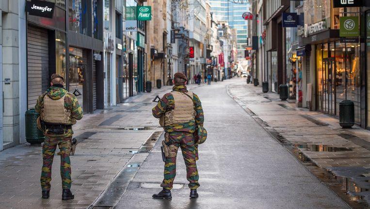 Militairen in een uitgestorven winkelstraat in Brussel. Beeld anp