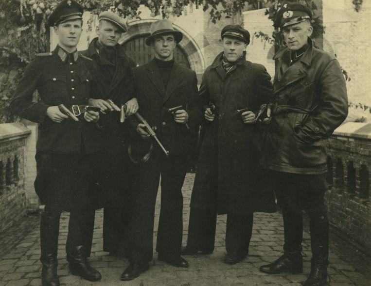 Piet Oberman (midden, met hoed) en Chris Hofing (rechts, politieuniform) op een foto uit 1945, kort na de bevrijding. Beeld