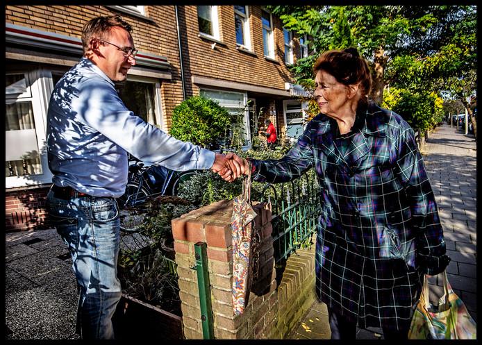 Richard de Mos wordt begroet door een buurtbewoner.
