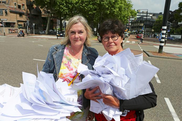 Els van der Rhee (l) en Gerdien van Nienes bedachten zich geen moment en begonnen, net als enkele andere omstanders, de papieren op te rapen.