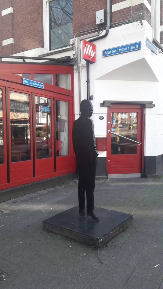 Het bord Plein Jules Deelder hangt aan de gevel van café Ari, waar ook het beeld van Deelder voor de deur staat.