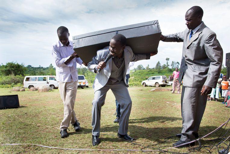 Een theatraal moment tijdens een begrafenis in Ramba, Kenia: Dominee Baba Dom verkondigt de angst voor de hel. De koffer symboliseert de schuld en boete die een mens op zijn rug kan dragen. Beeld Lieve Blancquaert