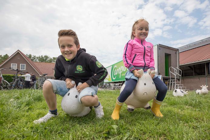 """Lucas en Isa de Rooij op koeien bij de Koeieboerderij van Melkveebedrijf """"Actie-Hove""""."""