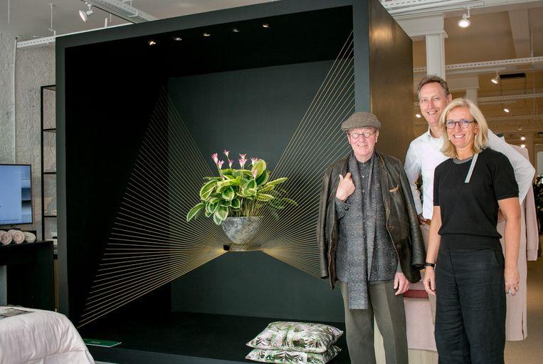 Daniël Ost met Patrick De Schepper en Griet Verlinden van Slaapgoed Verlinden in de Stationsstraat, waar dit werk van de bloemsierkunstenaar in de etalage staat.
