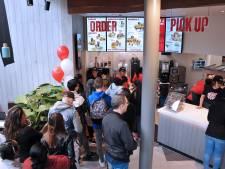 Eerste buckets en broodjes kip over de toonbank bij KFC Dordrecht