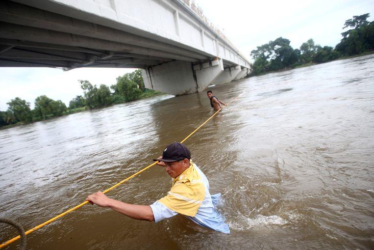 Een migrant uit Honduras probeert via de rivier Mexicaanse grond te bereiken. Beeld REUTERS