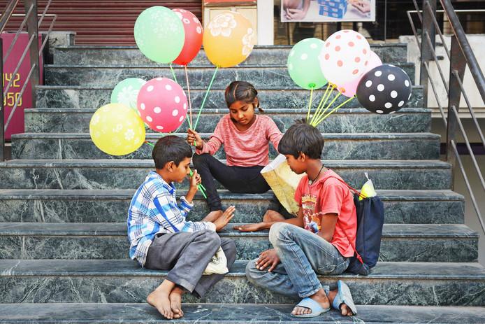 Indiase kinderen spelen op een trap in Amritsar met hun verdiende geld, terwijl ze wachten op nieuwe klanten voor de ballonnen die zij verkopen. Foto Narinder Nanu
