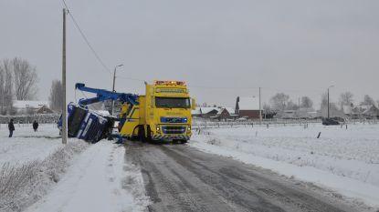 Vrachtwagen en auto schuiven in dezelfde straat in de gracht
