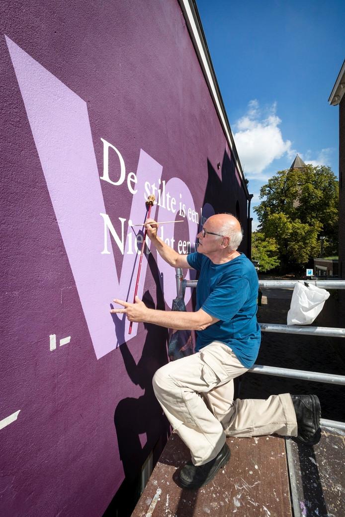 André Megens werkt aan de gevel aan de Clarastraat