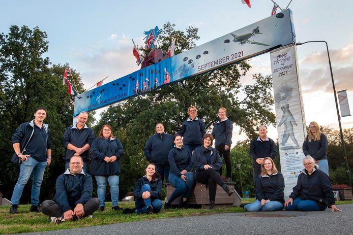 De leden van de Airborne Mallet Band bij de boog die jaarlijks wordt neergezet in Oosterbeek. De Airborne Wandeltocht mag dit jaar dan niet doorgaan, de leden gaan dit weekeinde wel aan de wandel.