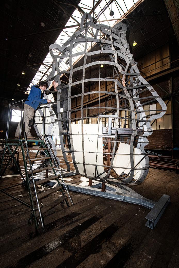 Kunstenaar Andreas Helfeld (l) en Gerard Kessel werken aan het Romeins masker in de werf aan de Rijndijk in Millingen.