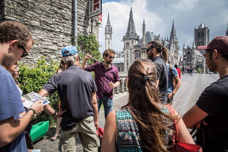 Een gids loodst een groepje toeristen rond in de 'wijze' stad van de Stroppendragers.