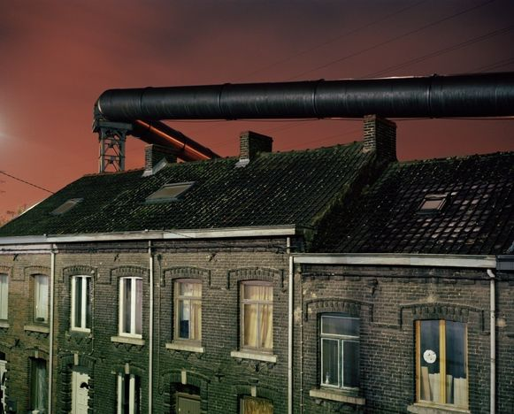 "Een voorbeeld uit de reeks: ""Gas supply tubes run along the houses built near the steel factories of Charleroi. Before the electric upgrade of the blast furnace, these tubes used to provide the energy needed for this operation."""