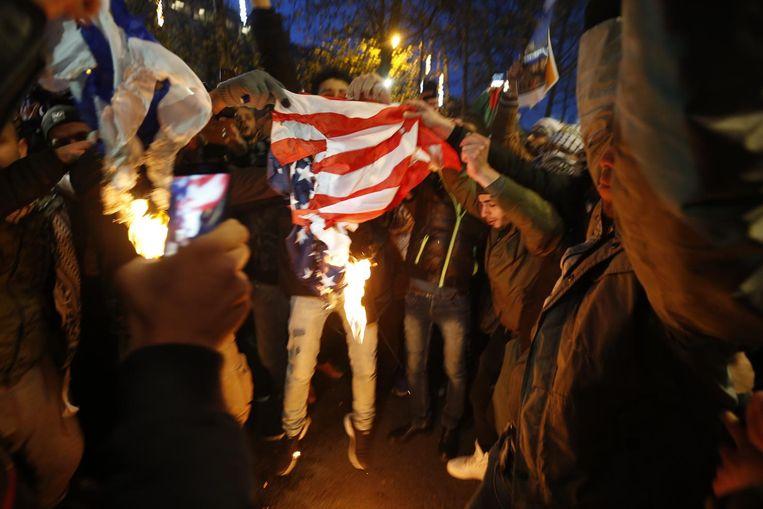 Bij een manifestatie voor de Amerikaanse ambassade in Brussel steken demonstranten een Amerikaanse vlag in de fik. Beeld belga