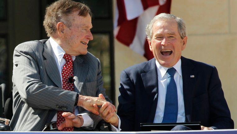 George H.W. Bush (links) schudt in Dallas de hand van zijn zoon George W. Bush. Foto uit 2013.