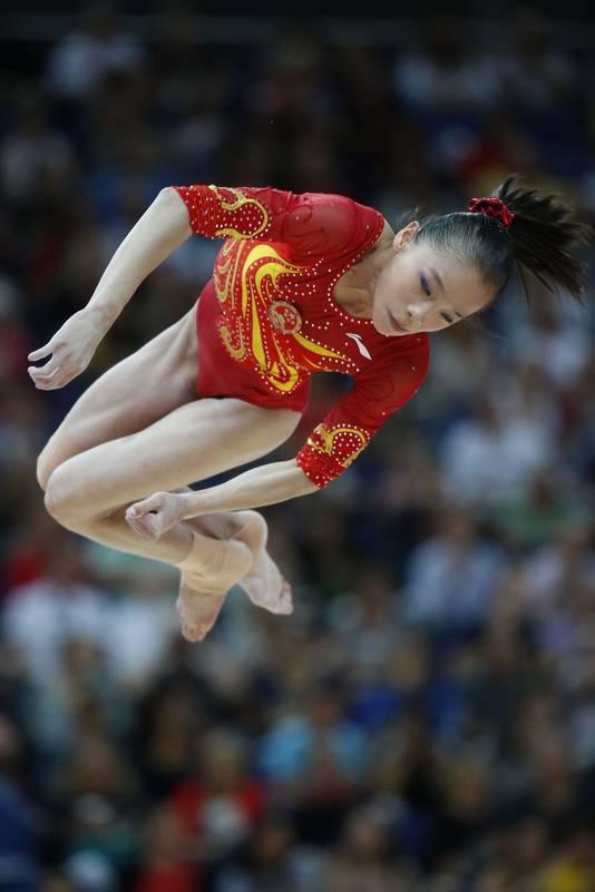 De Chinese Yao Jinnan heeft een rode scrunchie om haar lokken in bedwang te houden
