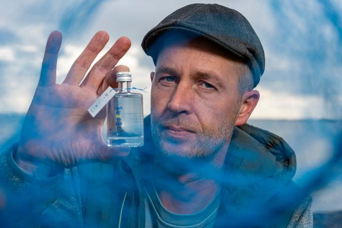 Vos Broekema met een flesje van zijn Zeeuws ruukwaeter Ooh de Zeê bij de Oosterschelde, waar hij praktisch langs woont