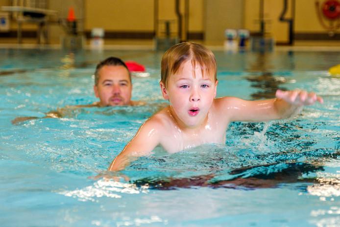 Een ouder geeft zijn kind zwemles in het Groenhovenbad in Gouda