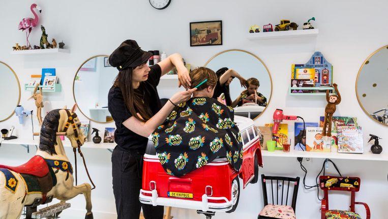 De klanten staan voor de kappersstoelkeuze: gaan ze voor de motor, de Volkswagenbus of het carrouselpaard? Beeld Tammy van Nerum