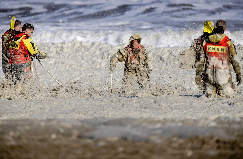 Leden van de KNRM trotseren het opvliegend schuim tijdens de hervatte zoektocht naar de vermiste watersporters bij het Noordelijk Havenhoofd.