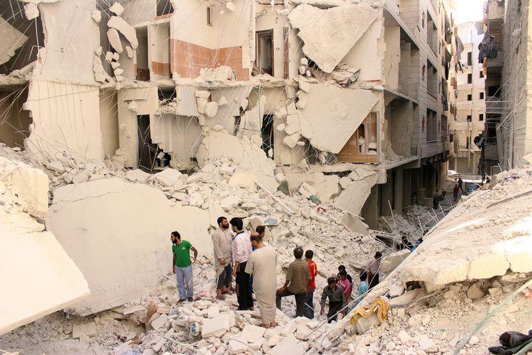 Syriërs inspecteren een ingestort gebouw in Aleppo. Beeld getty