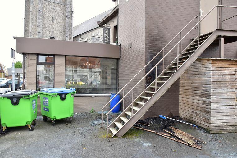 De muur vertoont achter de trap duidelijk de sporen van brandstichting.