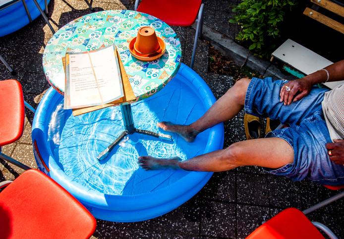 Een man zit met zijn voeten in een zwembadje op een terras.