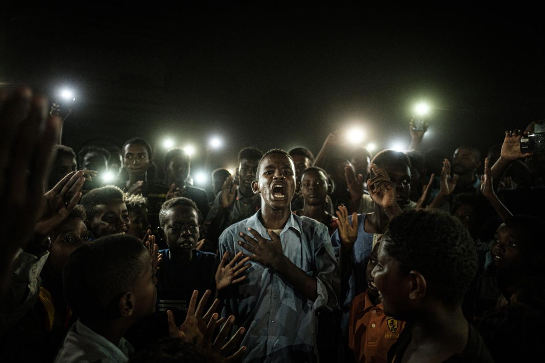 Bijgelicht door mobieltjes draagt een demonstrant een gedicht voor, tijdens de protesten in Soedan, afgelopen juni.