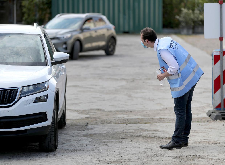 Coronabestrijding in Berlijn: een medewerker voert een gesprekje en voordat hij een testkit overhandigt in een drive-in testcentrum. Beeld AP