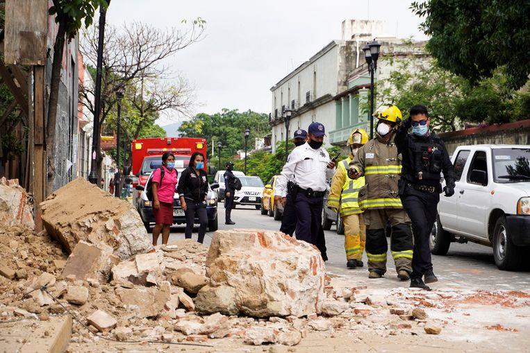 Politieagenten en brandweermannen inspecteren een gebouw in Oaxaca waarvan de muur is ingestort door de aardbeving. Beeld EPA