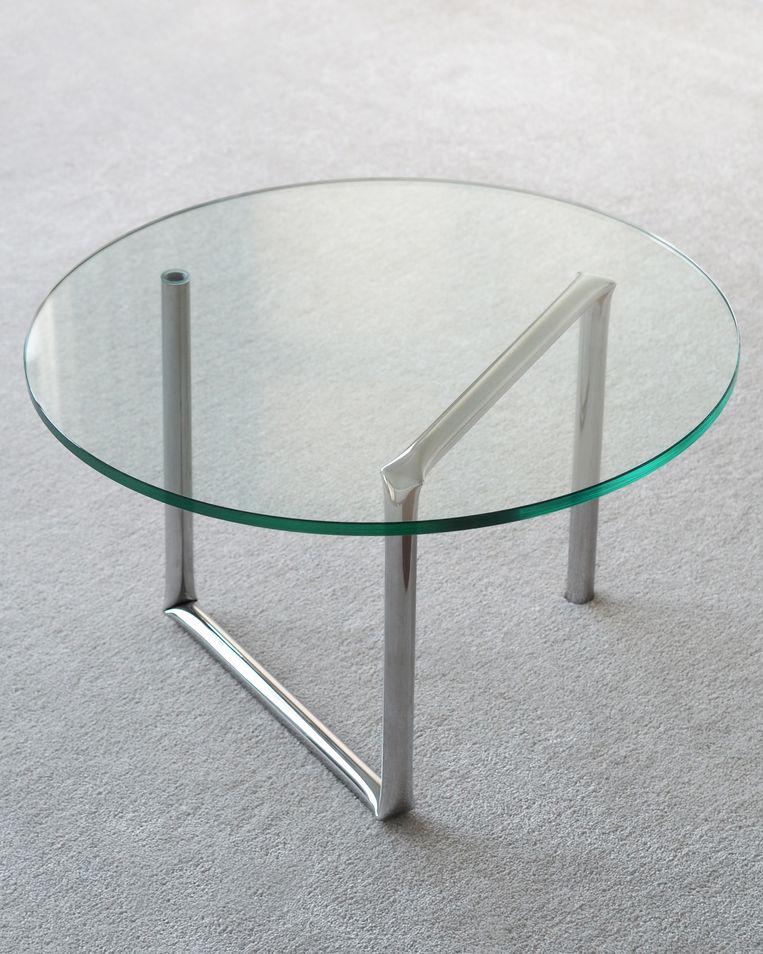 Tafel Salontafel 'Knik' is vernoemd naar de vier knikken in het roestvrijstalen frame. Diameter glazen tafelblad 70 cm, € 380. Beeld aetelier.ae