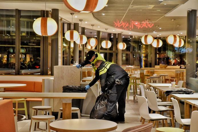 De politie controleert binnen in de McDonald's alle prullenbakken.