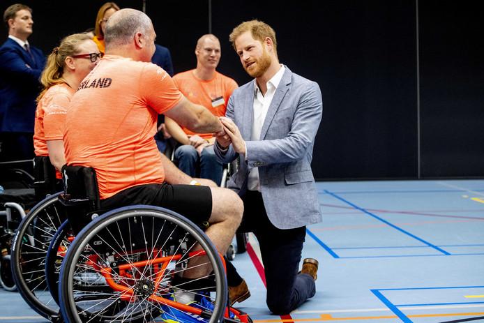 Prins Harry in gesprek met Eric Hartwich langs de kant van het veld bij een wedstrijd van het rolstoelbasketbal.