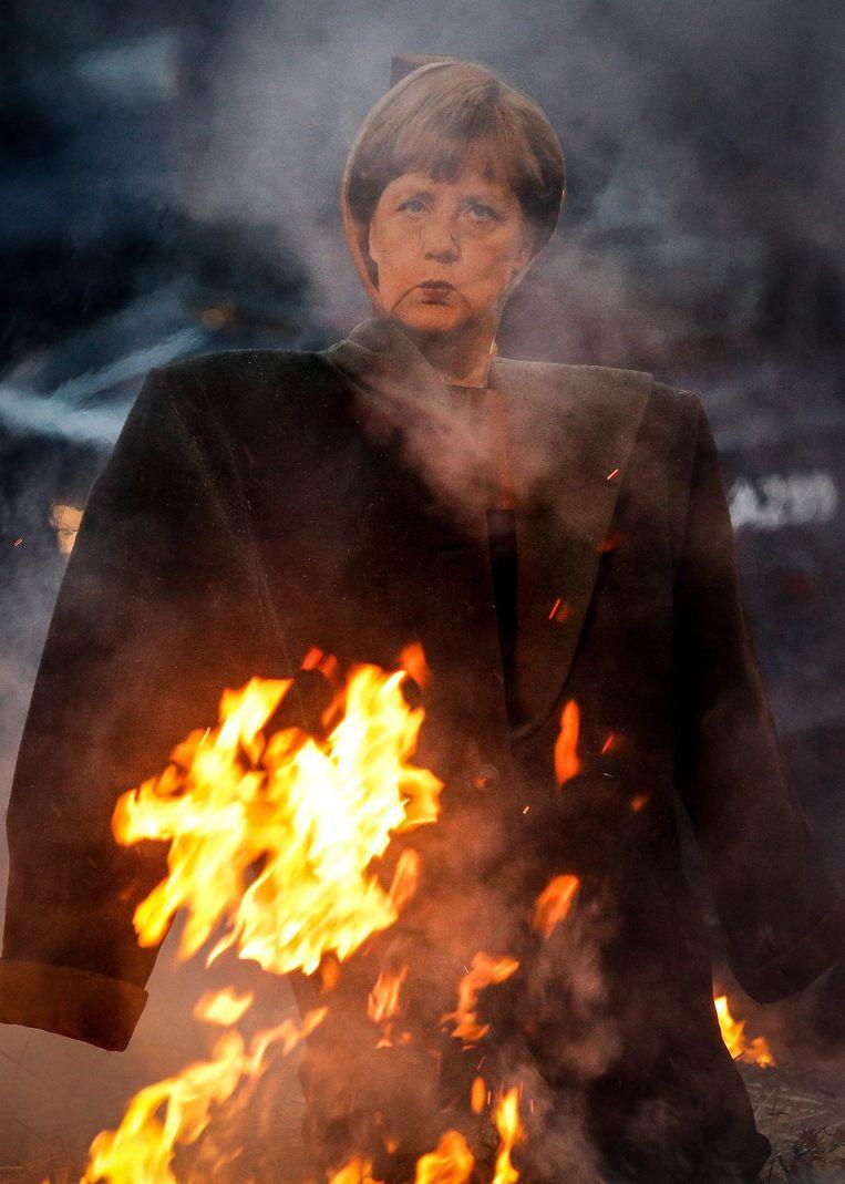Een Angela Merkel-beeltenis staat in brand bij een protest tegen TTIP in Brussel. Beeld anp