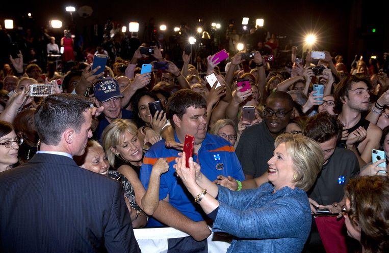 Hillary Clinton maakt een selfie op een campagnebijeenkomst. Beeld AP