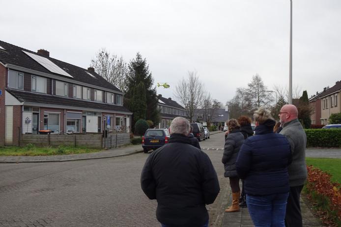 Bezorgde buurtbewoners kijken hoe een traumahelikopter arriveert.