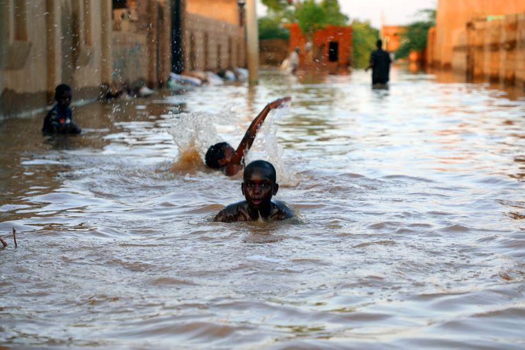 Kinderen zwemmen door de straat in Umm Dum, ten oosten van Khartoem, als gevolg van de zware overstroming van de Nijl in Soedan.   Beeld EPA