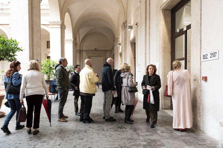 Italianen wachten in een rij voor het stemlokaal.  Beeld Marco Bonomo