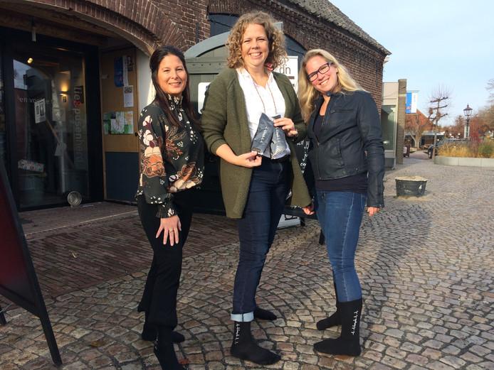 Josephine Bekkers, Penny Simons en Yvon van den Bosch tonen de sokken die nu al meer dan 700 euro opbrengen. Ten bate van het Rode Kruis.