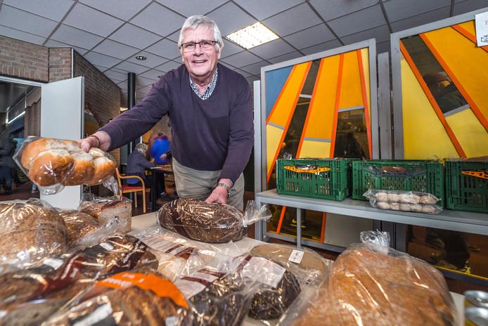 Voedselbank Delft-voorzitter Hans Mostert toont enkele producten die in de pakketten zitten.