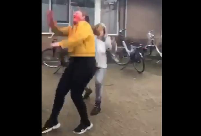 Videostill van het moment waarop de vrouw een van de meiden aan haar haren trekt. Daarvoor heeft ze haar al ondergespoten met rode verf.