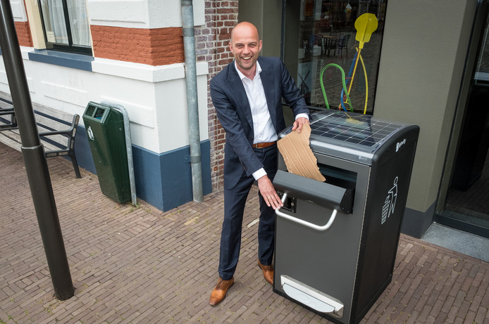 Wethouder Auke Schipper toont de nieuwe, slimme afvalbak. Het vervangt de 'oude, traditionele bak' (links).
