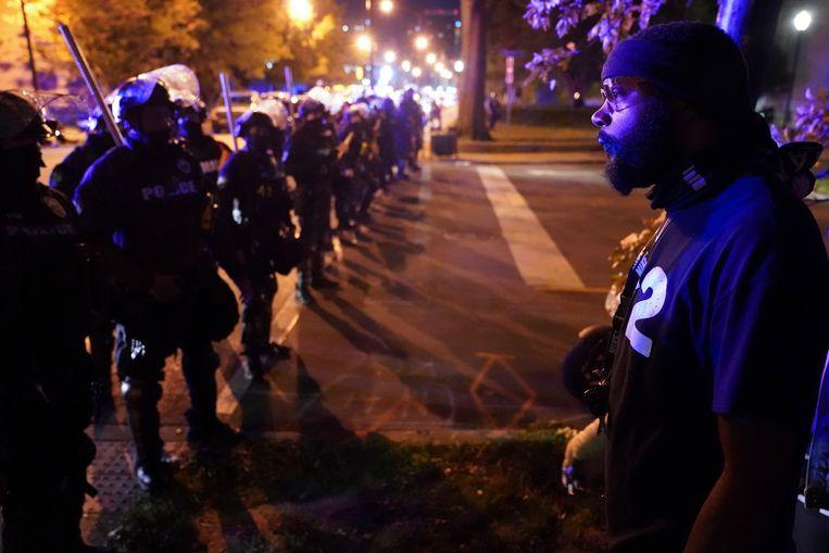 Een demonstrant staat oog in oog met een politiecordon in Louisville, tijdens betogingen tegen de beslissing om maar één agent te vervolgen voor de dood van Breonna Taylor. Beeld AP