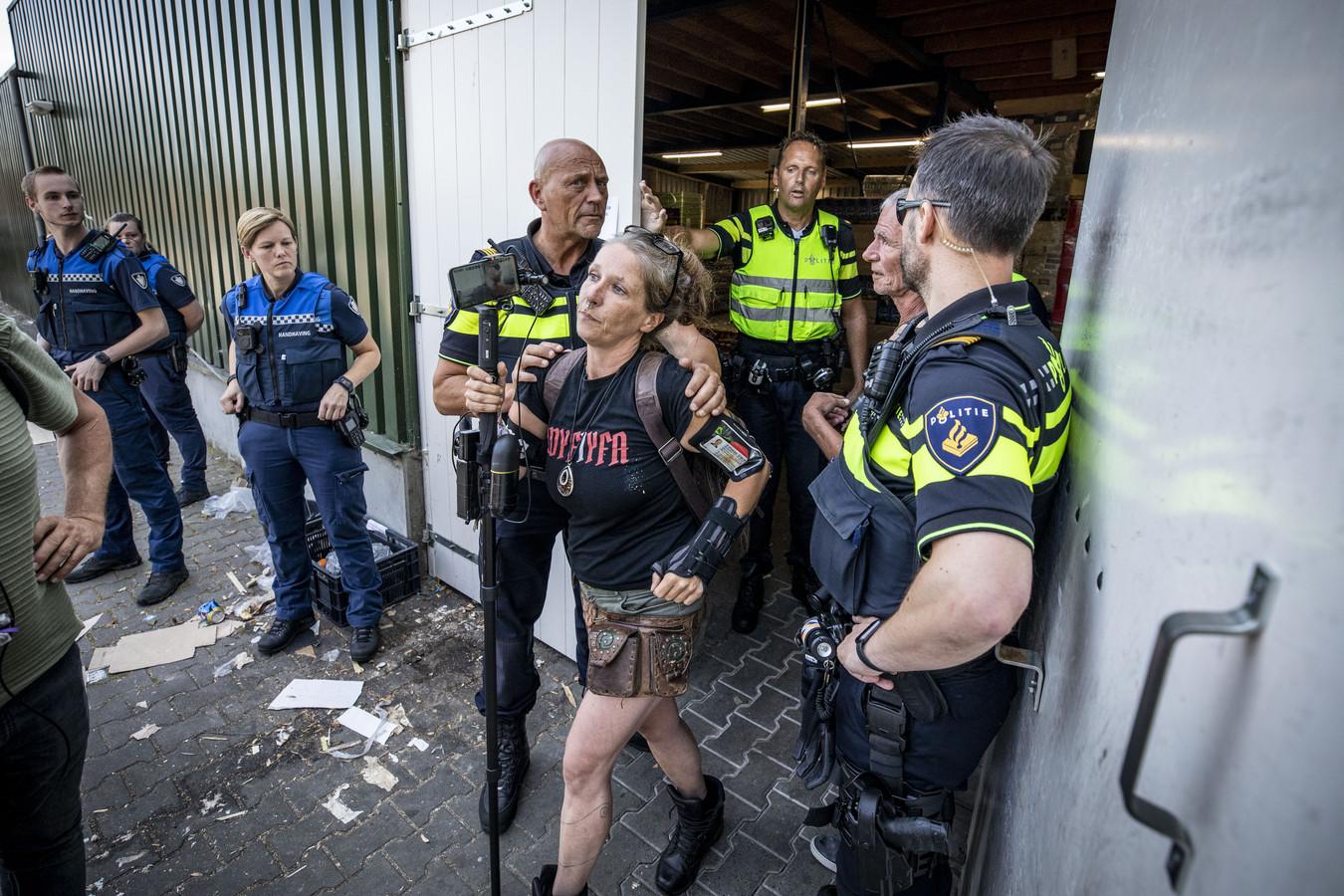 Steunbetuigers worden via de achteringang uit de supermarkt gehaald door de politie.