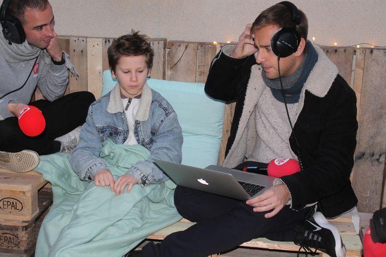 Q-Music-presentator Sam De Bruyn test de nieuwe cosy corner op de speelplaats uit, samen met de leerlingen van Jongslag.