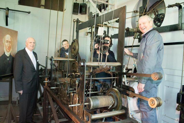 V.l.n.r.: Jos d'Haens, Christoffer Wendick, Hans Bontinck en Fons Dams bij de moederklok die het mechanisme van de Zimmertoren aanstuurt.
