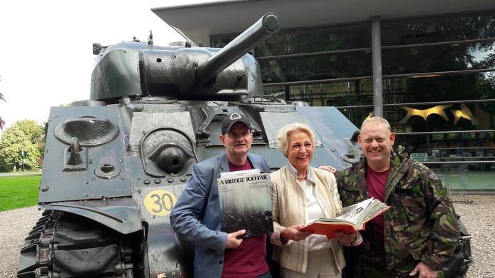 Voormalig productieassistent Reineke Kramer van  'A Bridge Too Far' poseert voor een tank bij het Airborne Museum Hartenstein in gezelschap van de makers van de nieuwe tv-serie Paratrooper. Links regisseur en filmproducent Lance Nielsen, rechts acteur Tony Fadil.